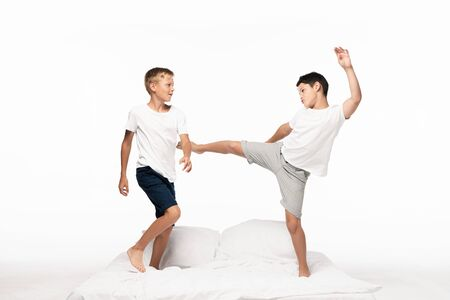 boy jokingly kicking brother with leg while having fun on bed isolated on white Reklamní fotografie