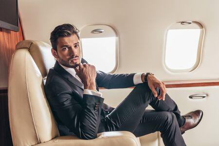 Gut aussehender Geschäftsmann im Anzug, der im Privatflugzeug in die Kamera schaut