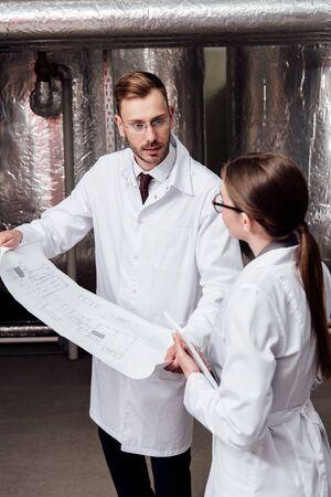ingegnere in camice bianco che guarda il collega mentre tiene il progetto