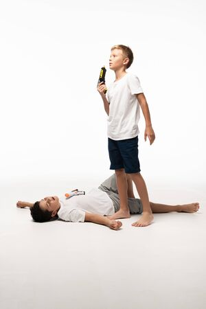 boy blowing at toy gun near brother pretending dead on white background