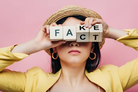 asian woman holding wooden cubes in front of face with fake and fact lettering isolated on pink Stock Photo