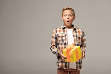 shocked boy holding yellow gift box and looking at camera isolated on grey 版權商用圖片