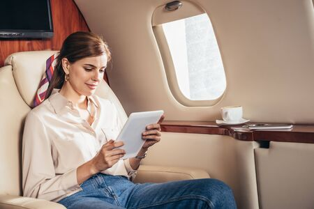 attractive woman in shirt using digital tablet in private plane