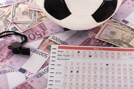 soccer ball, whistle and betting list on euro and dollar banknotes, sports betting concept