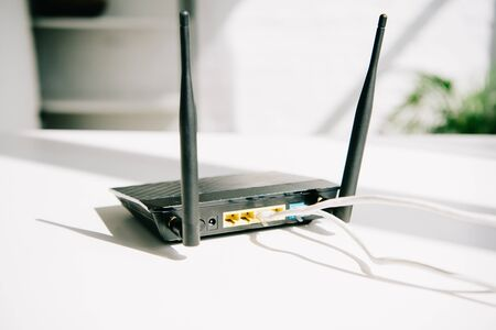 black plugged router on white office table in sunshine