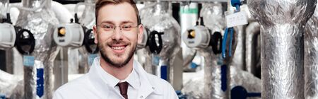 panoramic shot of happy bearded engineer in white coat near air compressed system