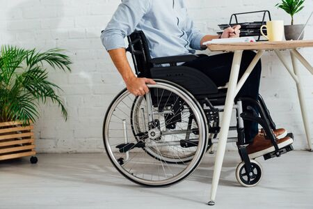 Cropped view of man in wheelchair writing in notebook at workplace Imagens