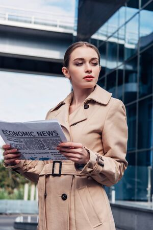 attractive woman in trench coat holding newspaper outside