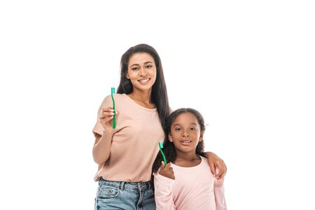 cheerful african american mother and daughter holding toothbrushes and smiling at camera isolated on white