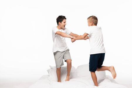 two brothers fighting for fun white standing on bed isolated on white