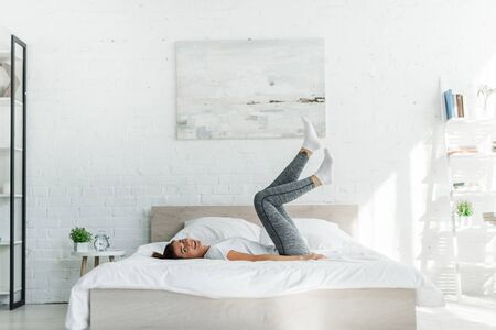 beautiful happy girl lying on bed in light bedroom Stock Photo