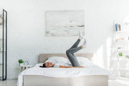 hermosa niña feliz acostada en la cama en el dormitorio de luz