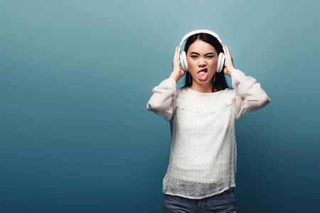 asian woman with headphones grimacing on blue background