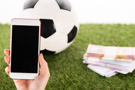 partial view of female hand with smartphone near packs of money and soccer ball on green grass isolated on white, sports betting concept Banque d'images