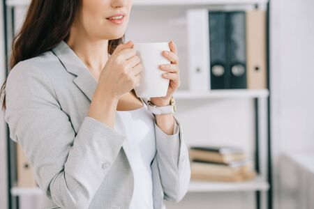 cropped view of young secretary holding coffee cup in office