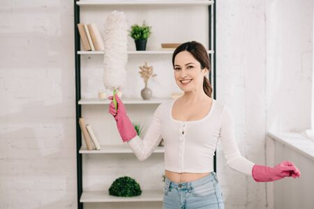 young, cheerful housewife looking at camera while holding dusting brush Archivio Fotografico