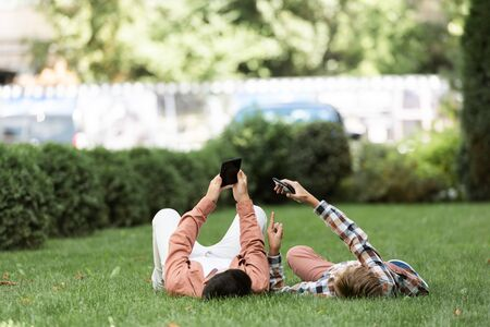 two brothers lying on green lawn on backs and using smartphones