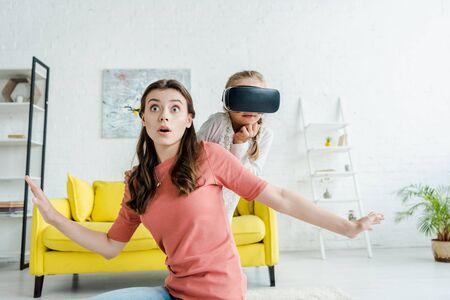 surprised babysitter with outstretched hands near kid in virtual reality headset