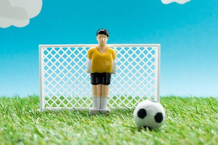 toy goalkeeper near miniature football gates and ball on blue background with clouds, sports betting concept Banco de Imagens