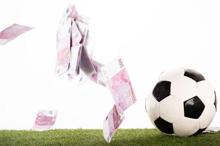 Fußball in der Nähe von fliegenden Euro-Banknoten isoliert auf weiß, Sportwetten-Konzept