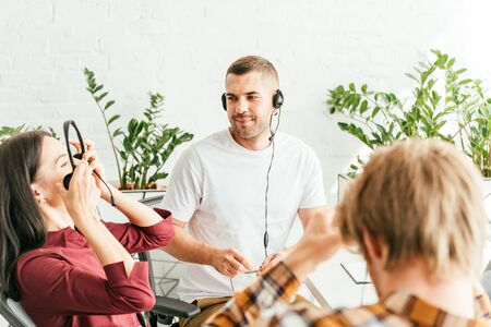 selective focus of broker wearing headset near coworkers in office