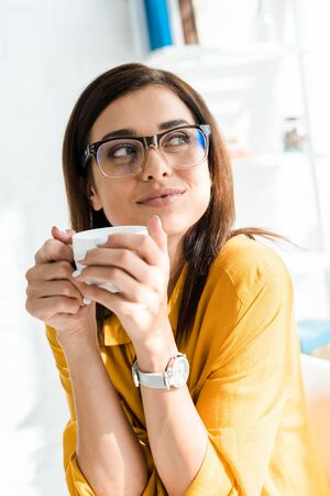 attractive pensive freelancer in eyeglasses holding cup of coffee in home office