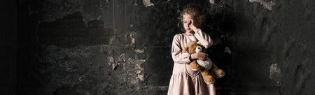 panoramic shot of frustrated kid crying while holding teddy bear in dirty room, post apocalyptic concept