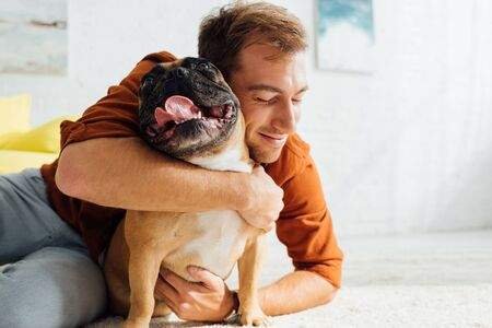 Smiling man hugging funny french bulldog on floor in living room Stok Fotoğraf