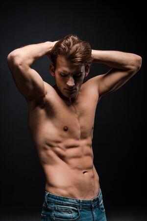 Mann mit nacktem Oberkörper zeigt Muskeln isoliert auf schwarz Standard-Bild