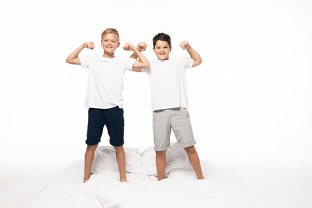 two brothers imitating bodybuilders while standing on bed isolated on white Imagens