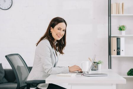 young, smiling secretary looking at camera while sitting at workplace in office
