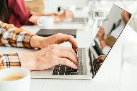 selective focus of broker typing on laptop keyboard near woman in office