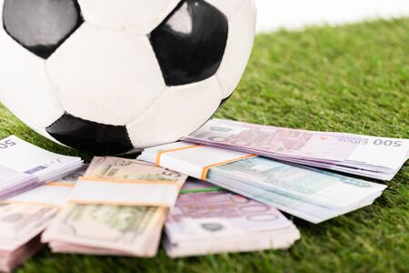 selective focus of euro and dollar banknotes near soccer ball on green grass, isolated on white, sports betting concept