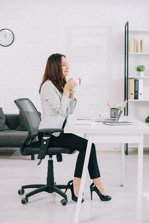 elegant, young secretary sitting at workplace with closed eyes while holding coffee cup