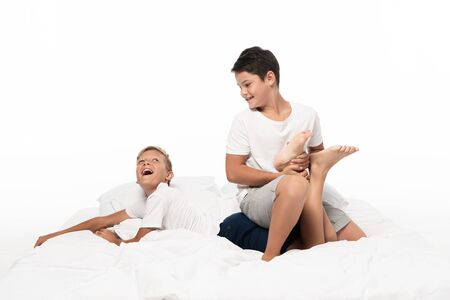 cheerful boy holding brothers leg while having fun on bed isolated on white