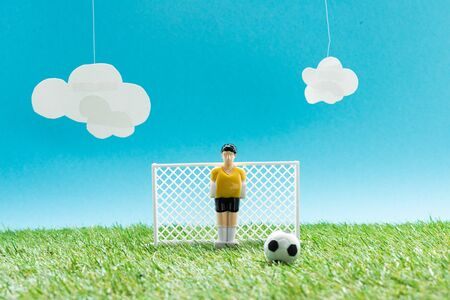 football field with toy goalkeeper near miniature football on blue background with clouds, sports betting concept