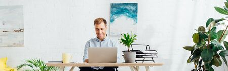 Smiling freelancer using laptop at desk in living room, panoramic shot Stockfoto