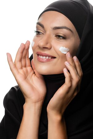 happy young Muslim woman in hijab applying cosmetic cream on chicks isolated on white Stock fotó