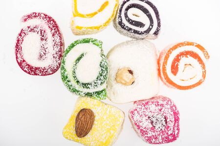 top view of assorted delicious turkish delight in coconut flakes isolated on white