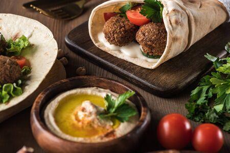 El enfoque selectivo de falafel con verduras y salsa en pita cerca de hummus en la mesa de madera