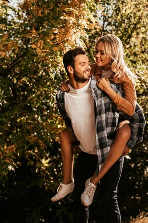 handsome, cheerful man piggybacking happy girlfriend in park