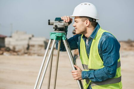 Side view of surveyor in hardhat looking throughout digital level on construction site
