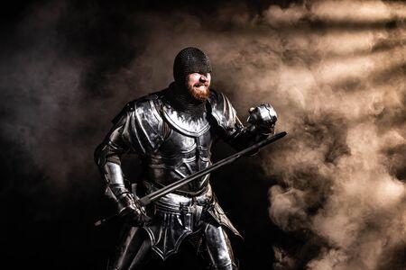 Apuesto caballero con armadura sosteniendo espada y luchando sobre fondo negro