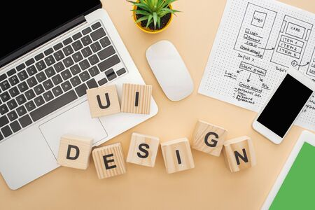 top view of gadgets near wooden blocks with ui design lettering, website design template and green plant on beige background Stock Photo