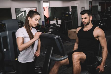 attractive trainer instructing handsome sportsman working out on recumbent elliptical trainer Stock Photo