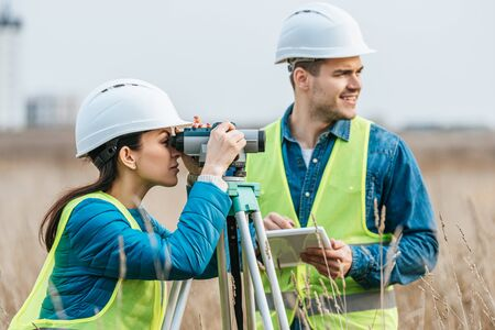 Surveyors working with digital level and tablet in field