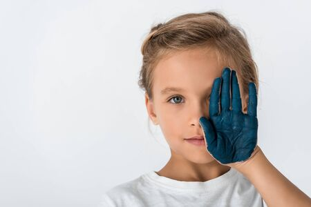 kid with blue paint on hand covering face isolated on white 免版税图像