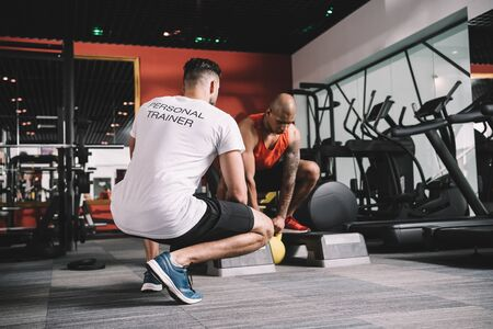back view of personal trainer supervising african american athlete lifting weight in gym Stock Photo