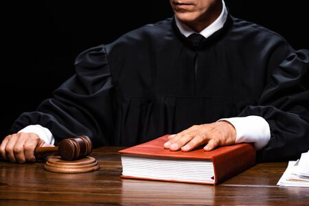 cropped view of judge in judicial robe sitting at table and holding gavel and book isolated on black