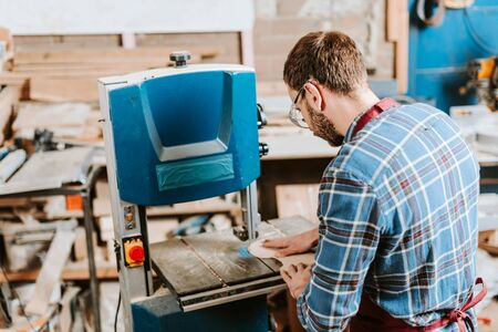bearded woodworker using cnc machine in workshop